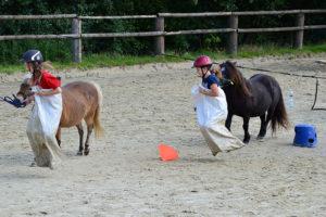 Kinder und Ponys hüpfen um die Wette. Wer gewinnt das Rennen?